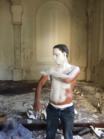 Ein Mann malt sich weiß an.