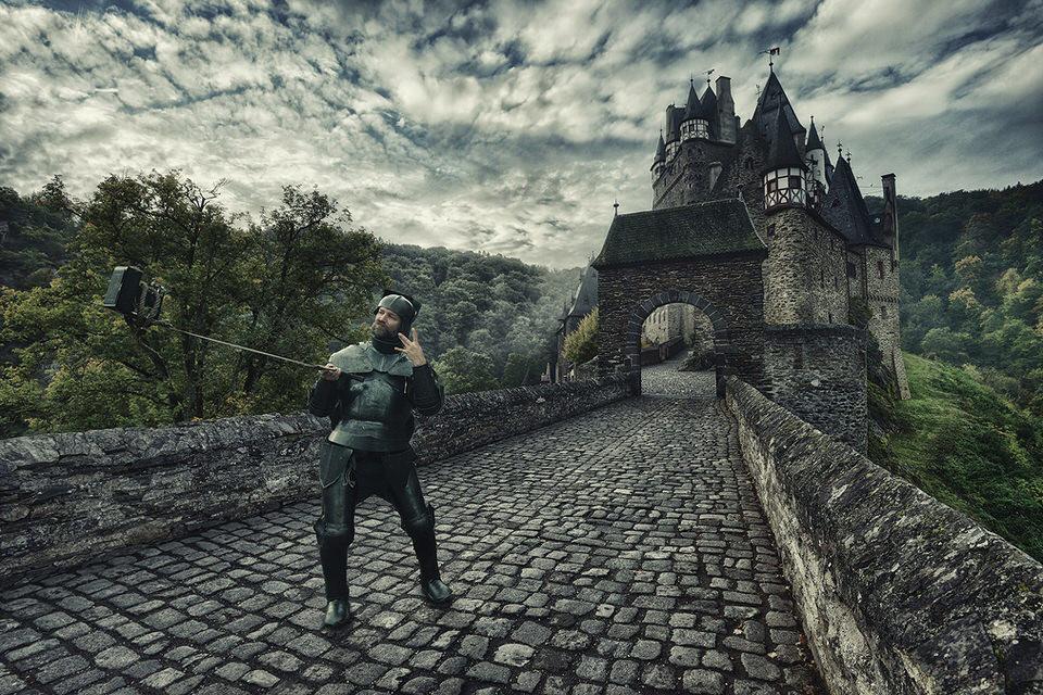 Ein Ritter mit Selfiestab vor einer Burg