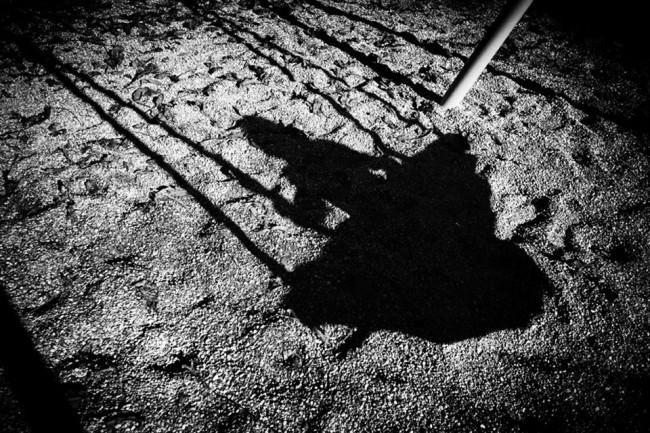 Der Schatten einer Netzschaukel im Sand.