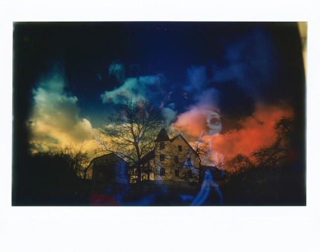 Bunte Doppelbelichtung mit einem Haus vor dramatischem Himmel und einer Plastikpuppe.