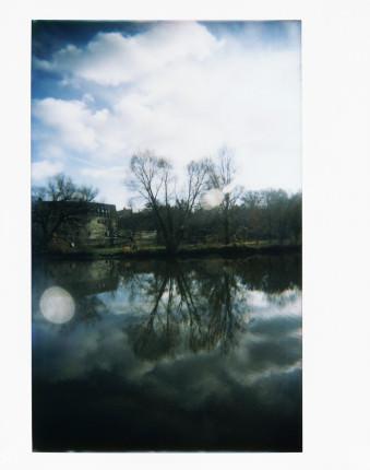 Eine Uferlandschaft spiegelt sich im Wasser.