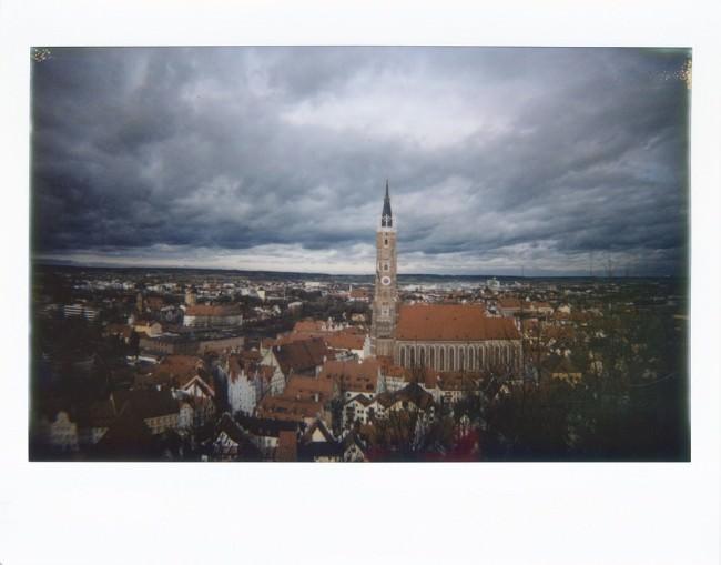 Blick über eine Kleinstadt mit dramatischem Wolkenhimmel.