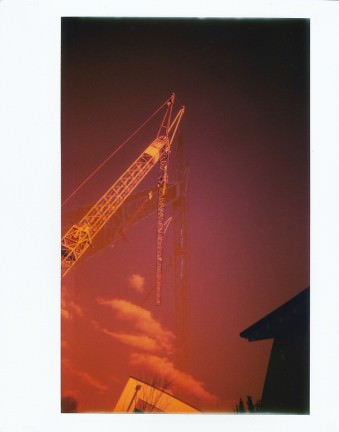 Pinkrote Aufnahme eines Krans vor Himmel mit wenigen Wolken.