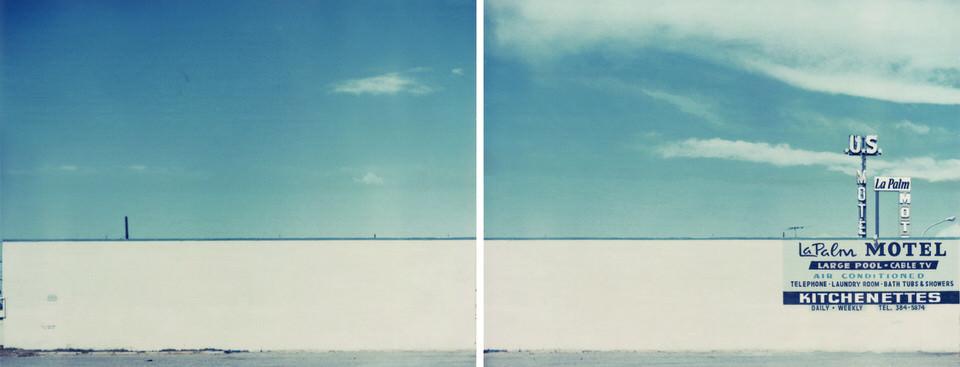 Eine Hauswand mit Werbeschild und blauem Himmel