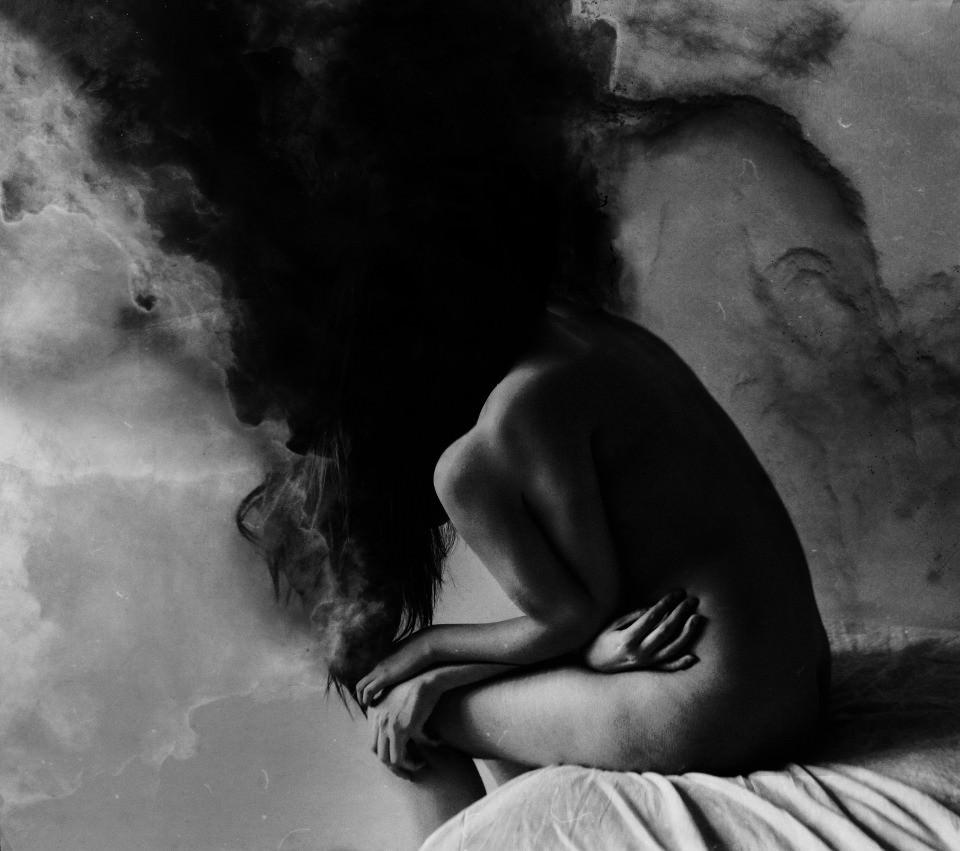 Eine nackte Frau mit vier Armen sitzt auf einem Bett, ihr Kopf ist schwarzer Rauch.