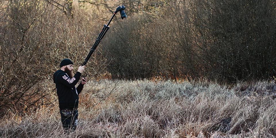 Ein mann hält ein Stativ mit Kamera in die Höhe