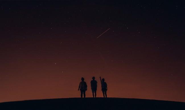 Drei Menschen als Silhouetten am Horizont vor einem Sternenhimmel.