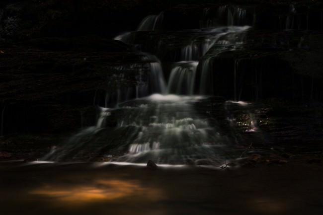 Dunkle Langzeitbelichtung eines Wasserfalls in einer Höhle.