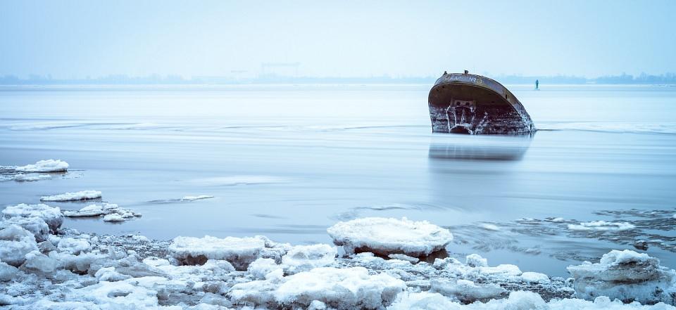 Schiffsrumpf ragt aus einem blauen Gewässer auf, am Ufer Schnee und Eis.