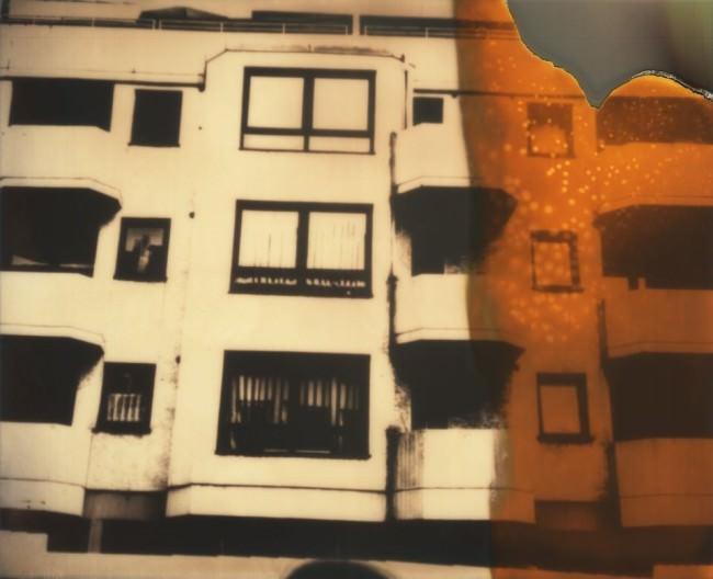 Polaroid einer Hauswand mit orangen Bildfehlern.