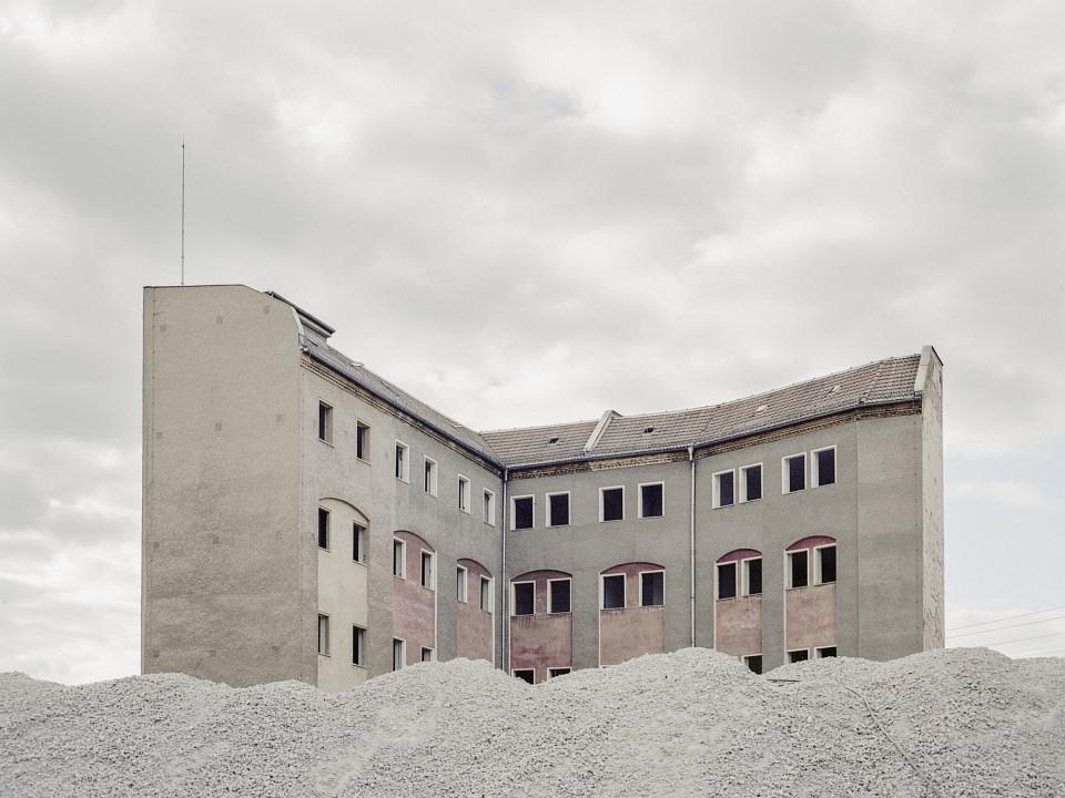 Graues Gebäude vor grauem Himmel hinter einem grauen Splitthaufen.
