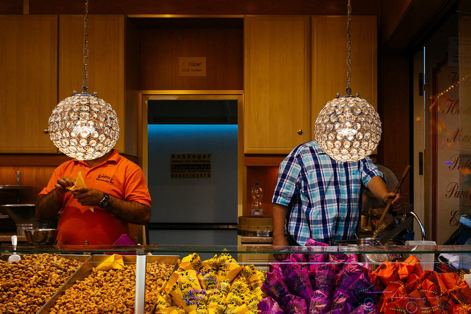 Zwei Menschen hinter dem Tresen eines Imbisses, die Köpfe von Lampen verdeckt.