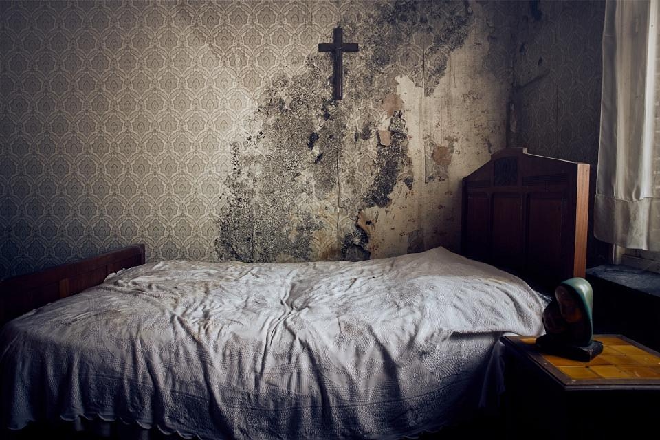 Schmutziges Bett vor einer verschimmelten Wand mit alter Tapete und einem Kreuz.