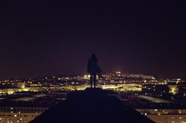 Frau steht auf einem schmalen Steg vor einer nächtlichen Stadtkulisse