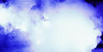 Ein Gitarrist steht fast vollständig von Nebel verhüllt auf einer Bühne.