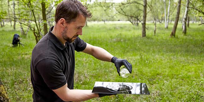 Eine Flüssigkeit wird auf eine Glasplatte geträufelt.