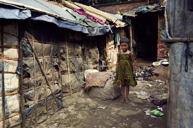 Ein Mädchen zwischen provisorischen Hütten
