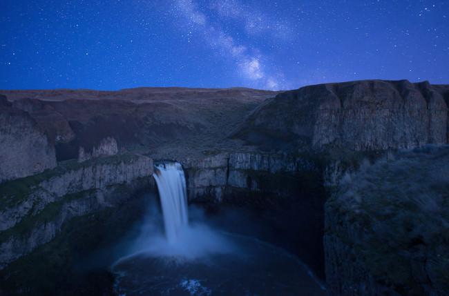 Nachthimmel mit Milchstraße vor einer Landschaft mit Wasserfall.