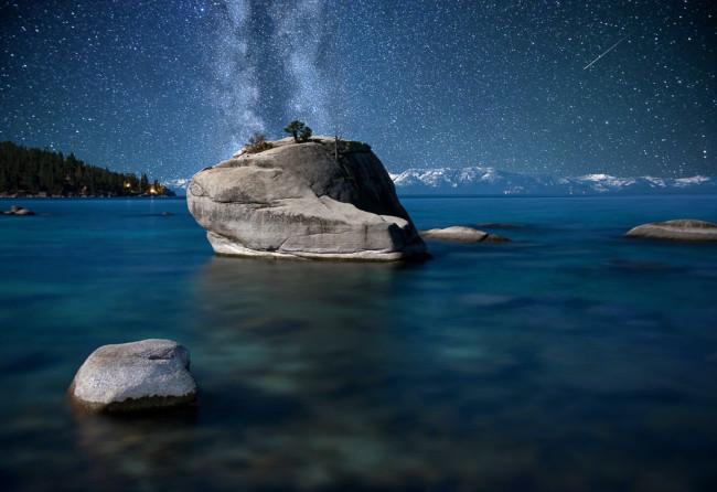 Nachthimmel mit Milchstraße über einem Gewässer, umgeben von Bergen.