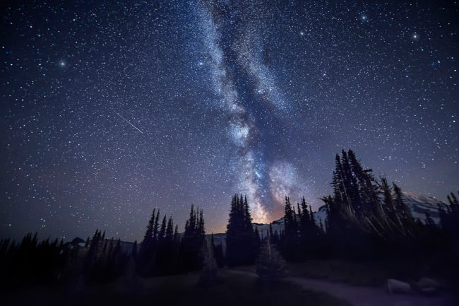 Nachthimmel mit Milchstraße und Sternschnuppe über einer Berglandschaft.