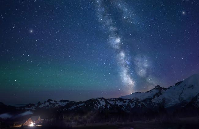 Nachthimmel mit Milchstraße über einer Berglandschaft.