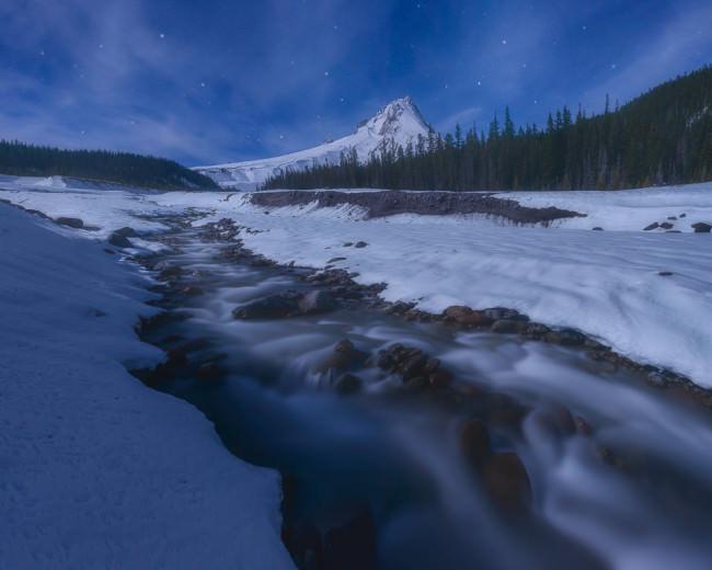 Ein Fluss windet sich durch eine verschneite Landschaft.