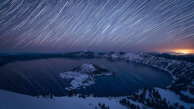 Nachthimmel mit Sternspuren über einem See in einer verschneiten Berglandschaft.