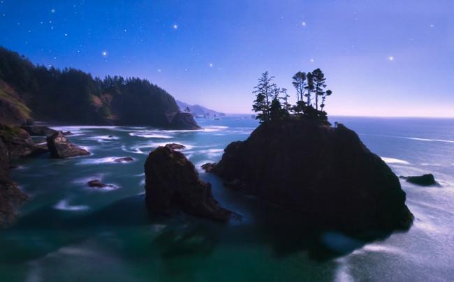 Landschaft mit Gewässer, Felsen, Wald und blauem Himmel mit Sternen.