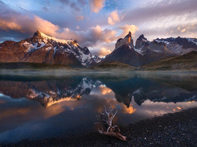 Bunter Himmel spiegelt sich in einem Gewässer vor einer Berglandschaft.