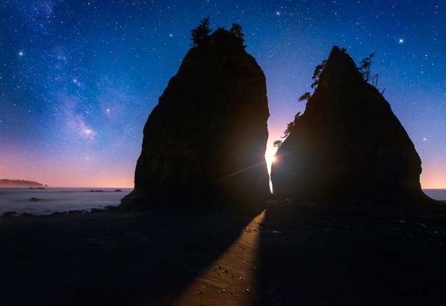 Sonne scheint zwischen zwei Felsen an einem Ufer hindurch.