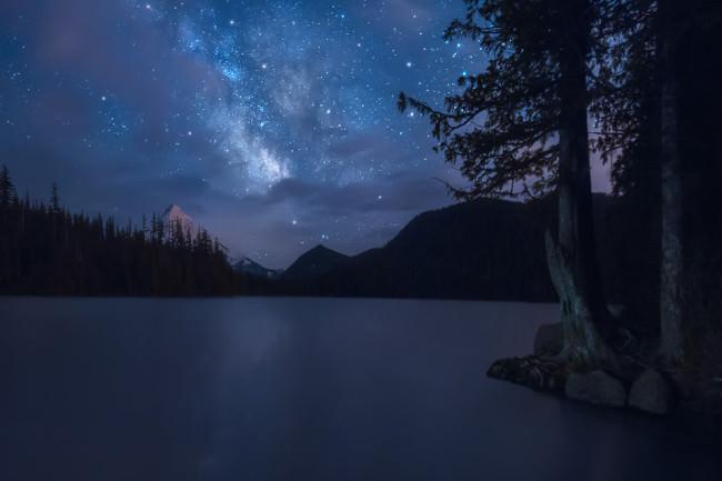Nachthimmel mit Milchstraße über einem See, umgeben von Bergen und Wald.
