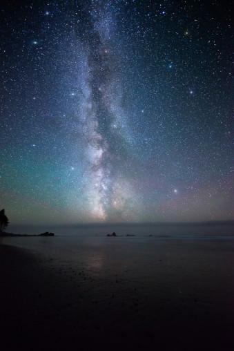 Nachthimmel mit Milchstraße über einem Gewässer.