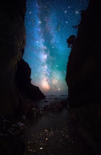 Nachthimmel mit Milchstraße, sichtbar in einer Schlucht zwischen zwei Felsen am Wasser.
