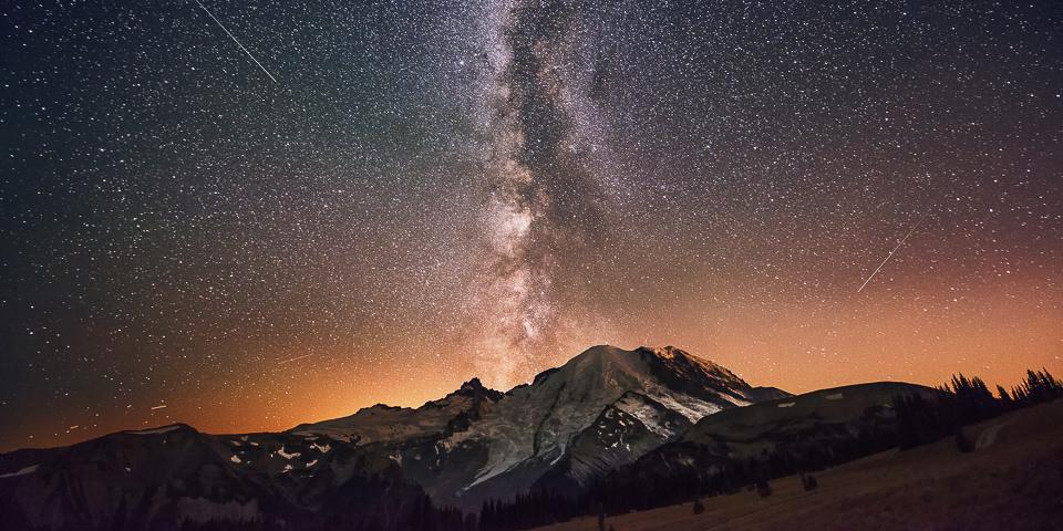 Nachthimmel mit Milchstraße üder einer Berglandschaft.