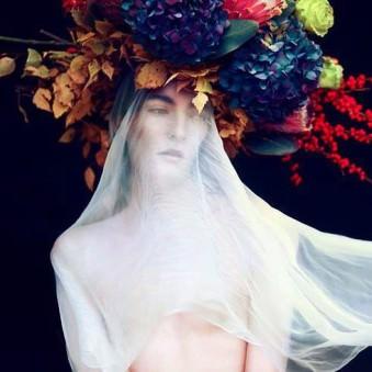 Mensch mit Blumengesteck auf dem Kopf und Schleier.
