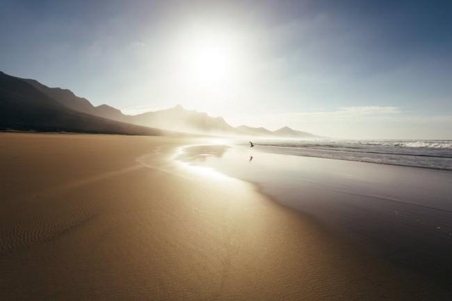 Strandlandschaft mit Bergen im Hintergrund, über die die Sonne strahlt.