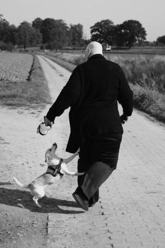 Eine Frau geht mit einem Hund spazieren.