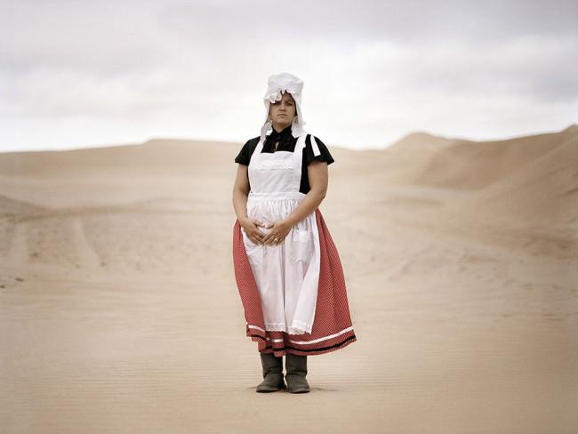 Ein Frau in Tracht in der Wüste