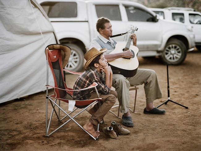 Ein Mann mit Gitarre und ein Junge auf Campingstühlen