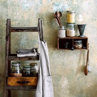 Leiter und kleines Regal vor einer Wand, gefüllt mit Gläsern und Küchengeräten.