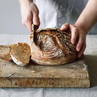 Hände schneiden einen Laib Brot.