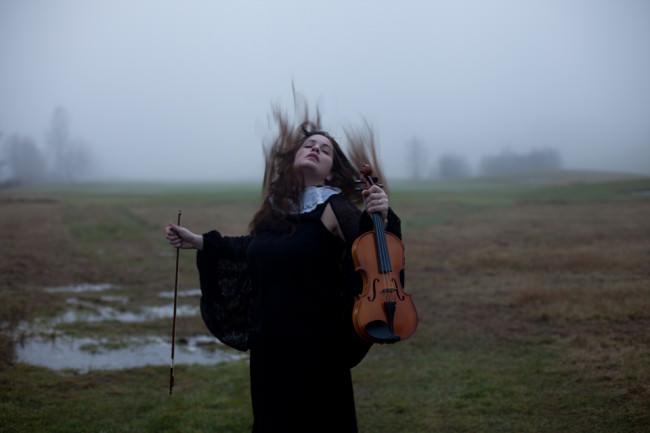 Ein Bild von einer Frau mit Geige auf einem Feld.