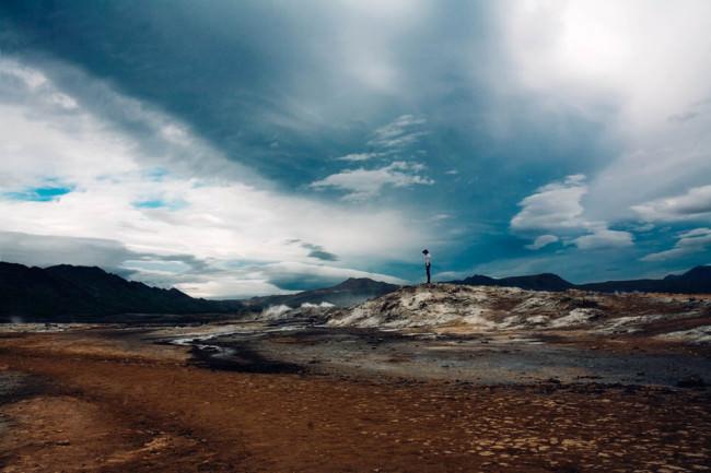 Ein Mann steht klein in einer surrealen Landschaft