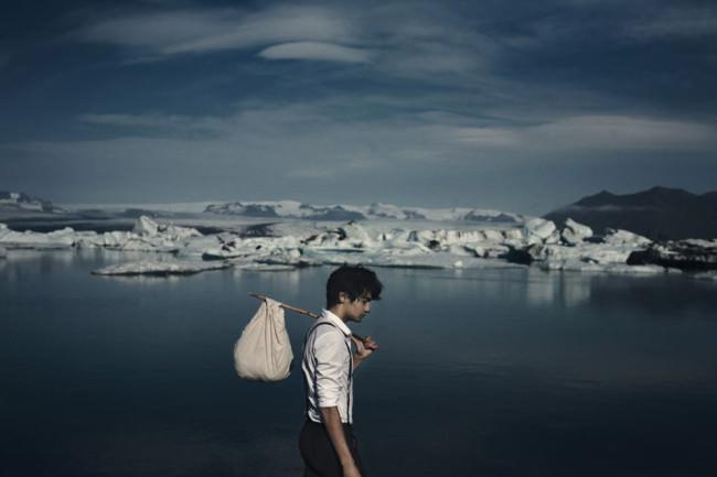 En Junge mit einem Stock und Tuch als Gepäck