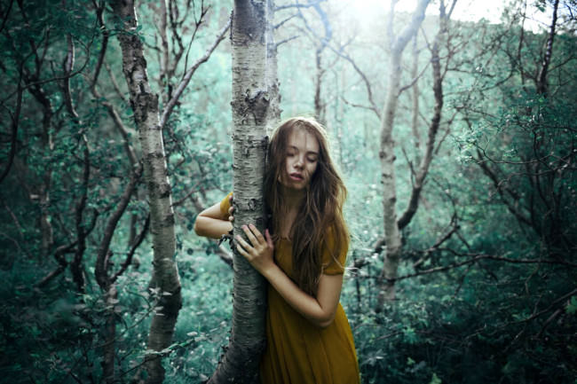 Eine Frau in einem türkisen Wald an eine Birke gelehnt.