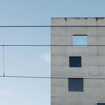 Betonwand mit Fenstern und Oberleitungen vor blauem Himmel.