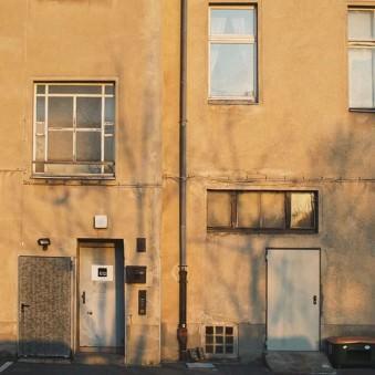 Fassade mit unterschiedlichen Fenstern und Türen in goldenes Sonnenlicht getaucht.