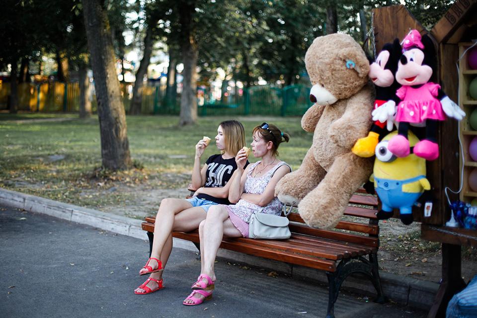 Zwei Frauen sitzen auf einer Bank und essen Eis.