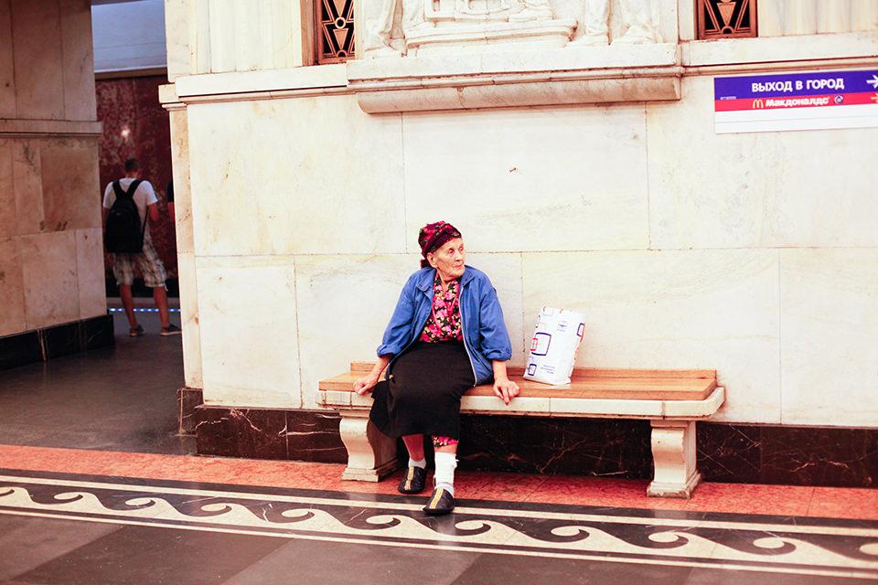 Eine alte Frau sitzt auf einer Bank und schaut nach rechts.