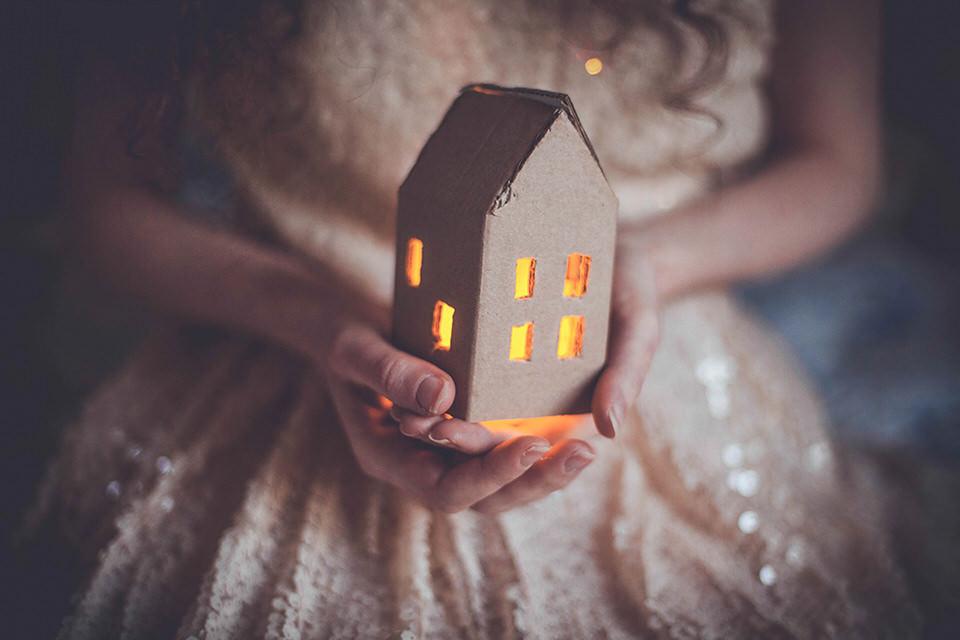 Ein beleuchtetes Häuschen in Händen
